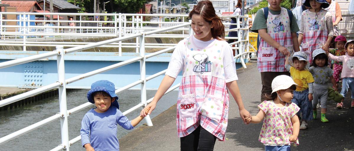 保育士と手をつなぎ川辺をお散歩する子供たち